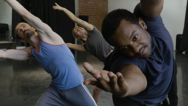 medium close-up shot of dancers bending over sideways stretching - bending over stock videos & royalty-free footage