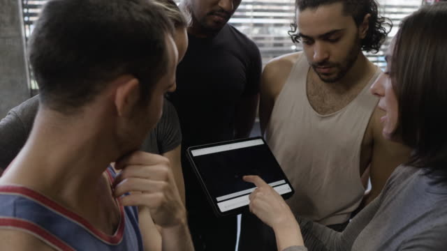 medium close-up shot of female choreographer showing choreography to dance troupe on tablet - dance studio stock videos & royalty-free footage