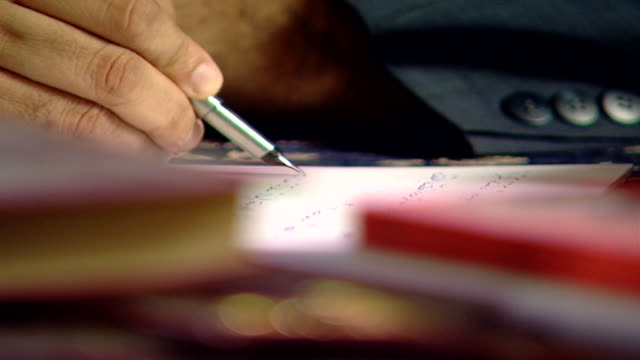 medium closeup view through books on a desk of a man's hand writing on paper in arabic with a fountain pen - pen stock videos & royalty-free footage