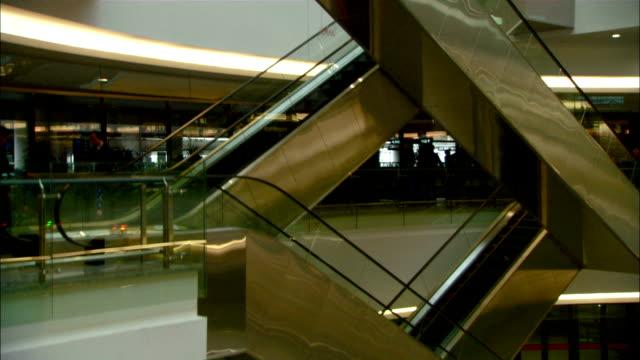medium crane - escalators form a pattern between levels in an atrium at the hongqiao hub./shanghai, china - flugpassagier stock-videos und b-roll-filmmaterial