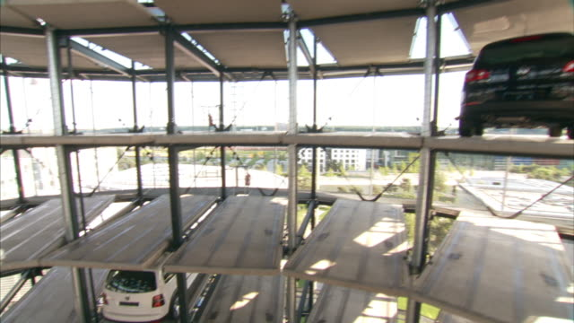 medium crane pan-right - cars fill parking spaces in a car tower. / wolfsburg, germany - wolfsburg lower saxony stock videos and b-roll footage