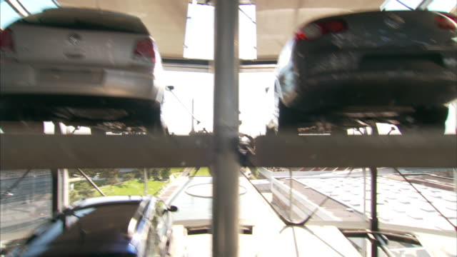 medium crane pan-right tilt-down - cars fill parking spaces in a glass-walled tower. / wolfsburg, germany - wolfsburg lower saxony stock videos and b-roll footage