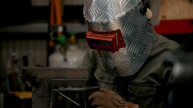 medium crane shot of a mid adult male welding and removing his helmet - welding helmet stock videos & royalty-free footage