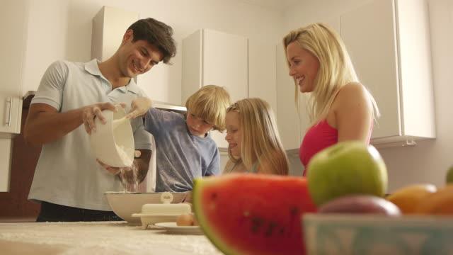 Medium dolly shot of family baking in kitchen/Sotogrande,Spain