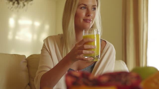 Medium dolly shot of woman drinking orange juice/Marbella region, Spain