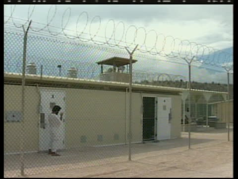 medium exterior shot seen through a fence of the camp delta section of guantanamo bay - crime or recreational drug or prison or legal trial stock-videos und b-roll-filmmaterial