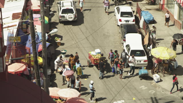 medium following shot of man wheeling fruit cart through busy market - guyana stock videos & royalty-free footage