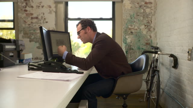 medium full shot. camera pushes in on profile of man at desk. he faces screen left. he is disappointed with what he sees on the computer screen and consequently bangs his head on the desk. - bestürzt stock-videos und b-roll-filmmaterial
