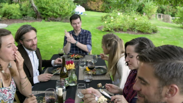 Medium group of people having an outdoor dinner party