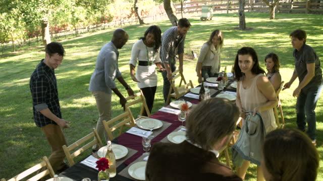 medium group of people taking seat at a table - tischflächen aufnahme stock-videos und b-roll-filmmaterial
