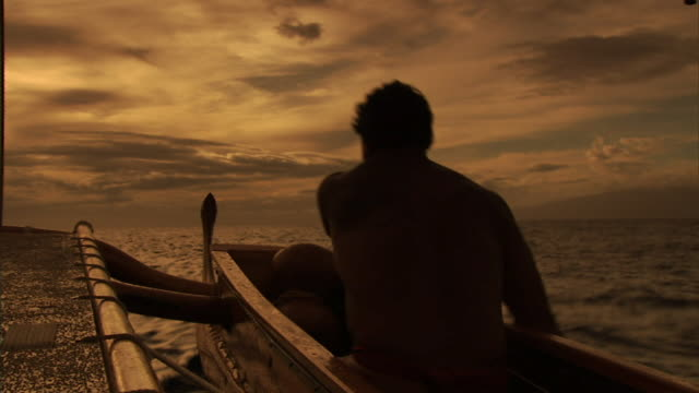 medium hand-held - a polynesian man rows a canoe over the ocean en route to hawaii. / hawaii, usa - north american tribal culture stock videos & royalty-free footage