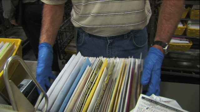 vidéos et rushes de medium hand-held - a postal worker sorts mail / santa clarita, california - facteur