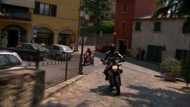 Medium hand-held - Motorcyclists drive along cobblestone streets in Italy. / Italy
