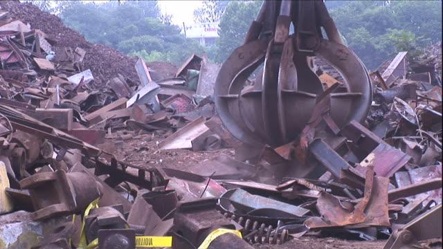 medium hand-held pan-left tilt-up - a crane picks up scrap metal / claymont, delaware  - crane stock videos & royalty-free footage