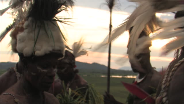 medium hand-held - papua new guinea natives in headdresses perform a welcome dance. / papua, new guinea - papua stock videos and b-roll footage