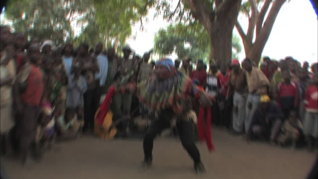 vídeos de stock e filmes b-roll de medium hand-held push-in - an audience surrounds a masked dancer in mozambique. / mozambique - moçambique