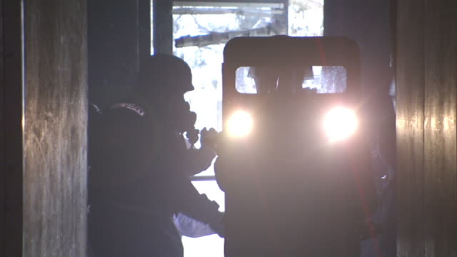 medium hand-held - riot police use shields and flashlights as they enter a dark building. / virginia, usa - campo di allenamento militare video stock e b–roll