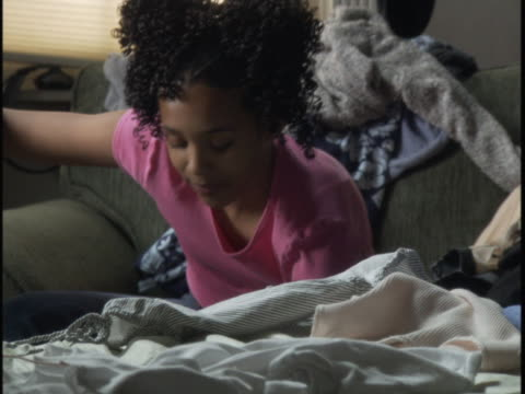 vidéos et rushes de medium handheld shot of a teenage girl as she digs through her laundry in her bedroom - messy bedroom