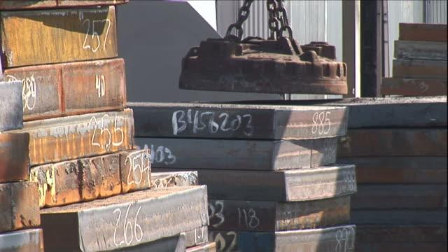 Medium hand-held tilt-up - An electromagnet picks up a steel slab at a steel factory / Claymont, Delaware