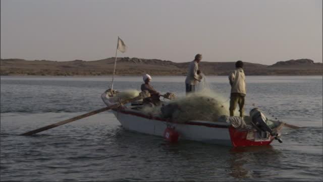 medium, hand-held tracking-left - fishermen row a boat to shore / egypt - 男漁師点の映像素材/bロール
