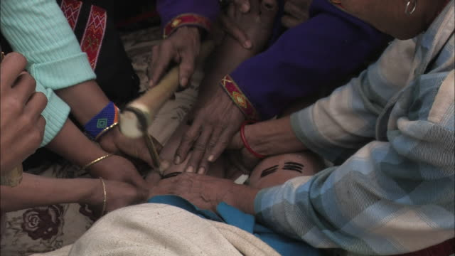 medium hand-held - village members restrain a man while a tattoo artist uses a native tool to tap ink into the skin. / india - human limb stock videos & royalty-free footage