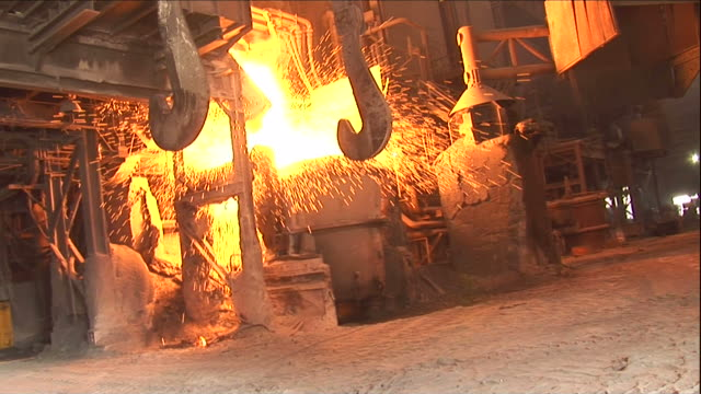 medium hand-held zoom-in - molten metal pours into a bucket / claymont, delaware  - steel mill stock videos & royalty-free footage