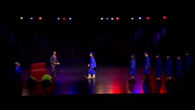 medium high angle of graduates walking across stage to receive their diplomas. - diploma stock videos & royalty-free footage