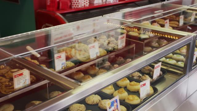 medium high angle panning shot of bakery display case / salt lake city, utah, united states - skåp med glasdörrar bildbanksvideor och videomaterial från bakom kulisserna