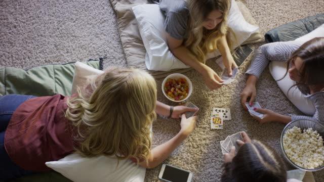 Medium high angle panning shot of girls laying on floor playing cards / Cedar Hills, Utah, United States