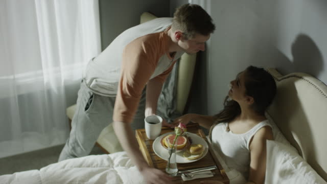 vidéos et rushes de medium high angle panning shot of man serving woman breakfast in bed / cedar hills, utah, united states - règle de savoir vivre