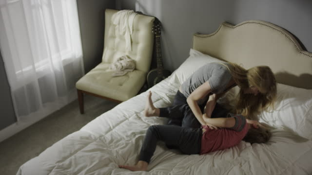 vidéos et rushes de medium high angle panning shot of mother tickling son on bed / cedar hills, utah, united states - chatouiller