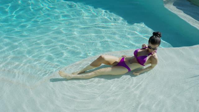 Medium high angle panning shot of woman relaxing in pool / Cedar Hills, Utah, United States