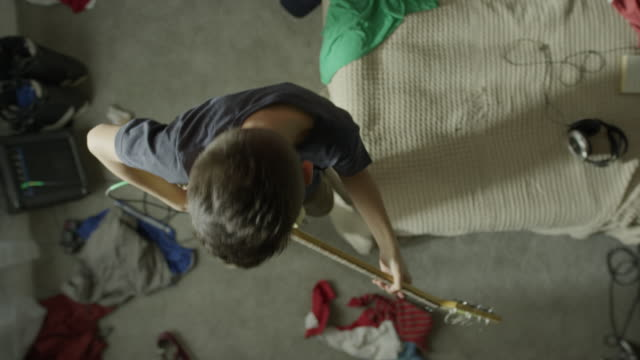 Medium high angle shot of boy playing guitar in messy bedroom / Cedar Hills, Utah, United States