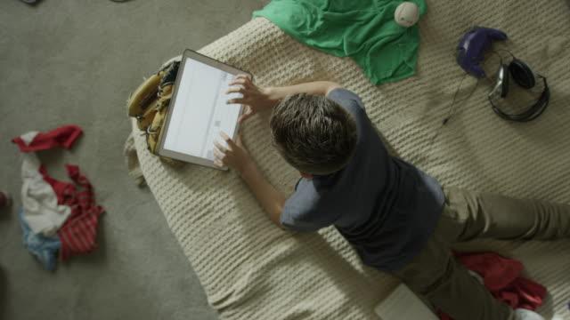 medium high angle shot of boy using digital tablet in bed / cedar hills, utah, united states - 寝室点の映像素材/bロール