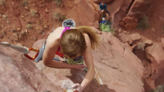 Medium high angle shot of climber fastening rope to carabiner / Fisher Towers, Utah, United States
