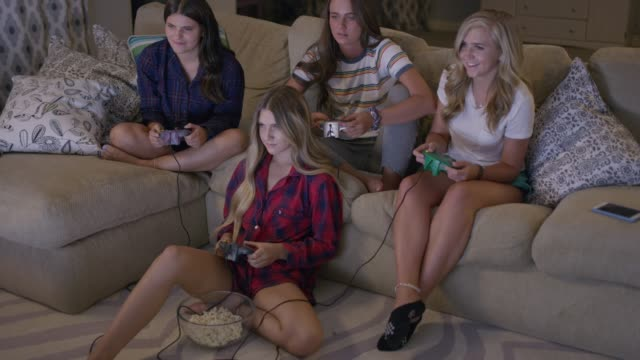 medium high angle shot of girls playing video game at slumber party / cedar hills, utah, united states - endast unga kvinnor bildbanksvideor och videomaterial från bakom kulisserna
