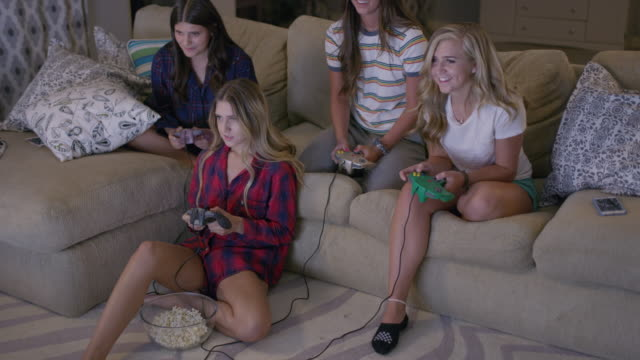 medium high angle shot of girls playing video game at slumber party / cedar hills, utah, united states - slumber party stock videos and b-roll footage