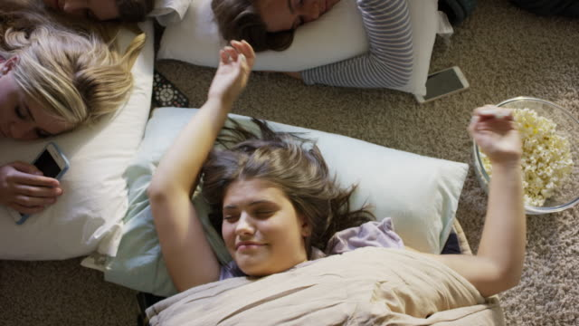 medium high angle shot of girls sleeping on floor and waking at slumber party / cedar hills, utah, united states - slumber party stock videos and b-roll footage