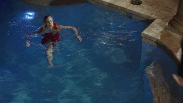 Medium high angle shot of man in shirt and tie jumping in pool / Cedar Hills, Utah, United States