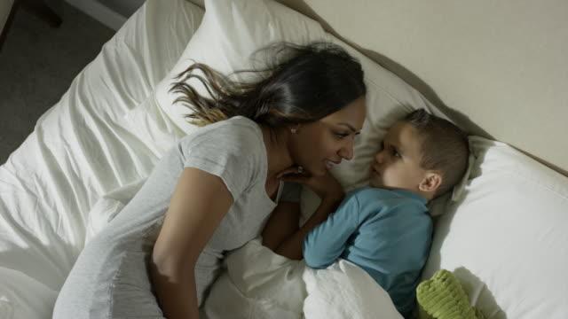 medium high angle shot of mother and son talking in bed / cedar hills, utah, united states - 横向きに寝る点の映像素材/bロール