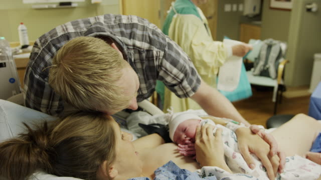 Medium high angle shot of parents admiring newborn baby in hospital / Midvale, Utah, United States