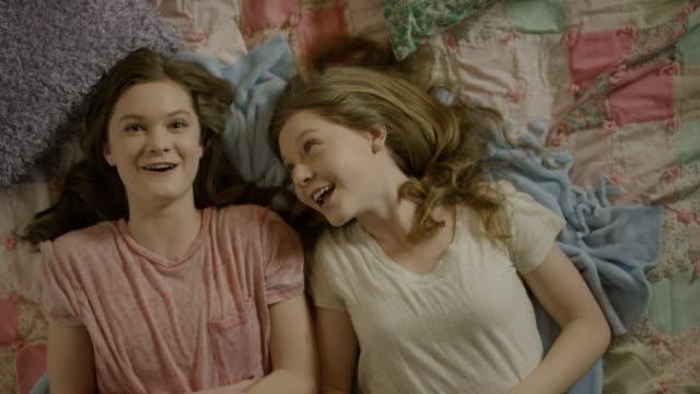 """medium high angle shot of teenage girls talking on bed / cedar hills, utah, united states"" - only teenage girls stock videos and b-roll footage"