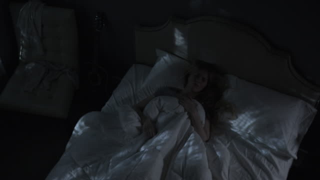 vídeos de stock, filmes e b-roll de medium high angle time lapse panning shot shot of woman having nightmares in bed / cedar hills, utah, united states - assustador