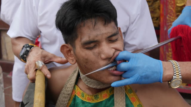 medium, in a trance, get extreme piercings and walk in a procession during the phuket vegetarian festival in phuket thailand. - piercing stock videos & royalty-free footage