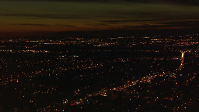 Medium Long Shot aerial pan,left push,in , City lights illuminate a suburb of New York City at night. / New York City, New York, USA