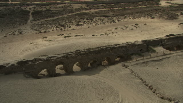 medium long shot aerial pan-left tracking-right - an aqueduct spans a beach in israel. / israel - caesarea stock videos & royalty-free footage