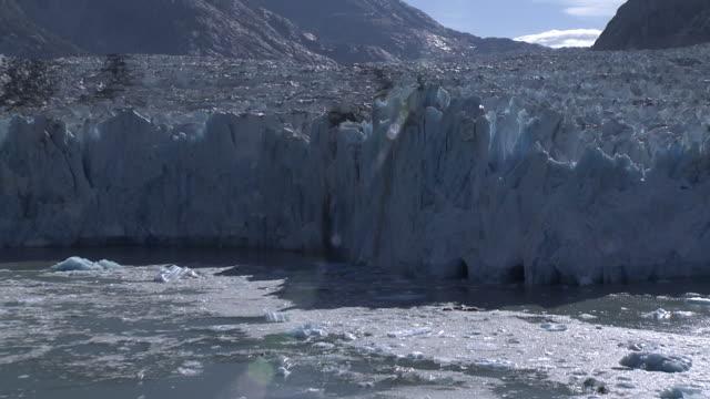 'Medium Long Shot aerial push-in tilt-up tracking-left-Bright sunlight shines on a jagged glacier. / Alaska, USA'