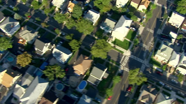 Medium Long Shot  aerial tracking-left - Rows of houses fill a suburban neighborhood. /  USA