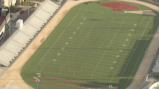medium long shot aerial tracking-left zoom-in zoom-out - an athletic complex includes empty football and baseball fields and bleachers. / los angeles, california, usa - アメリカンフットボール場点の映像素材/bロール