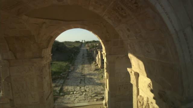 medium long shot crane - a ruinous archway frames a narrow road at leptis magna. / khoms, libya - old ruin stock videos & royalty-free footage
